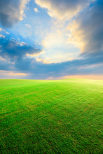 Green Grass Field And Colorful Sky Clouds At Sunset.