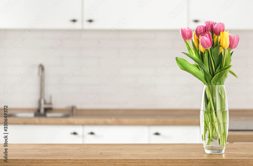 Fototapeta Bouquet of beautiful tulips on the kitchen table top on blur kitchen background with place for montage product display
