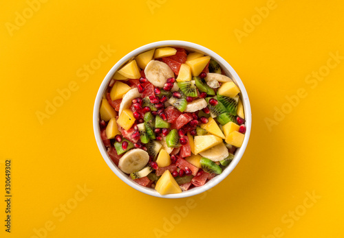 Mixed fruit salad in plate on yellow background top view Diet summer food concep Wallpaper Mural