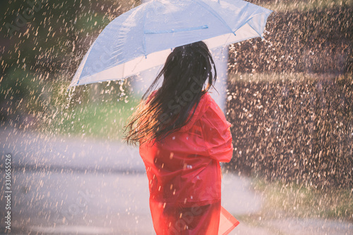Foto Asian children spreading umbrellas playing in the rain, she is wearing rainwear