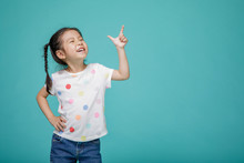 Beautiful Smiling Asian Little Girl Pointing Hand To Blank Speech Bubble, Empty Space In Studio Shot Isolated On Colorful Blue Background, Educational Concept For School