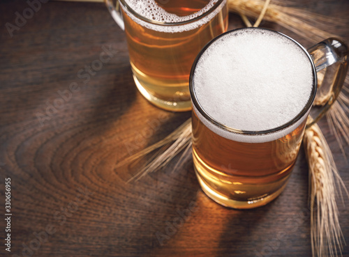 Платно Glasses of Light Beer with wheat on the wooden table, copy space for your text