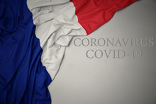 Waving National Flag Of France With Text Coronavirus Covid-19 On A Gray Background.