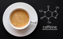 Blackboard With The Chemical Formula Of Caffeine, Close Up Cup Of Fresh Coffee On Black Background. Top View With Copy Space