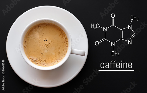 Foto Blackboard with the chemical formula of caffeine, close up cup of fresh coffee on black background