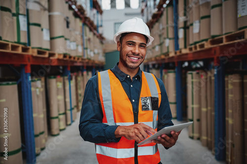 Happy male factory manager using digital tablet in warehouse while standing agai Fototapete