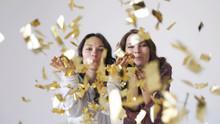 Two Beautiful Girls Blowing Gold Glitter Confetti On A White Background