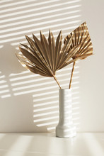 Dry Plants In Minimalistic Ceramic Jar With Horizontal Sunlight Stripes On White Wall Through Blinds. Vertical Image Of Paper Flowers In Stylish Vase On Office Desk. Decoration And Interior Design