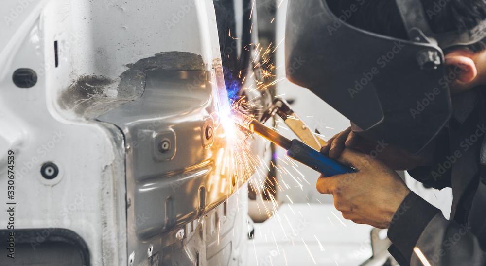Fototapeta Worker welds car. Metalworking with carbon dioxide welding.
