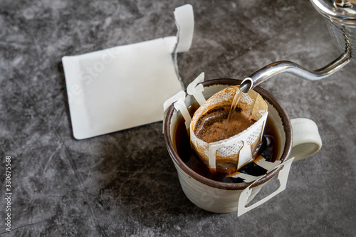 Photo Pouring water on coffee grind ,coffee drip bag and pottery mug on stone table ba