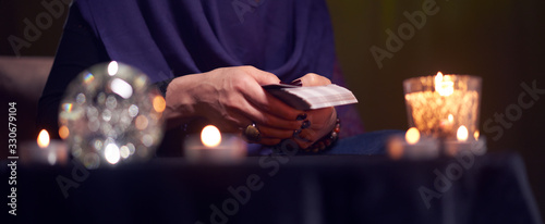 Fortuneteller woman divines on cards sitting at table with burning candles, magi Wallpaper Mural