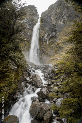 Vertical picture of Devils Punchbowl Waterfall surrounded by greenery in New Zealand
