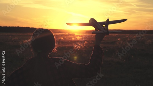 Photo Happy girl runs with a toy airplane on a field in the sunset light