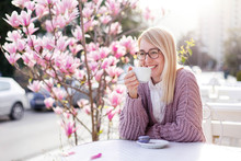 Spring Cafe. Young Woman Drinking Coffee At City Streets. Attractive Happy Girl Smiling And Enjoying Sunset Outdoors. Blooming Bushes Of Pink Magnolia Flowers. Lifestyle Moment.