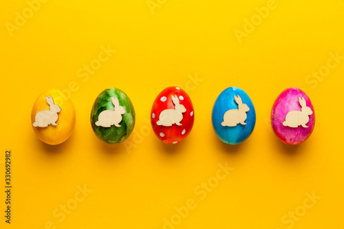Bright easter eggs with bunny (rabbit) on yellow background Canvas Print