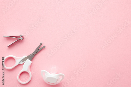 Scissors, clipper and soother on light pink table Canvas-taulu