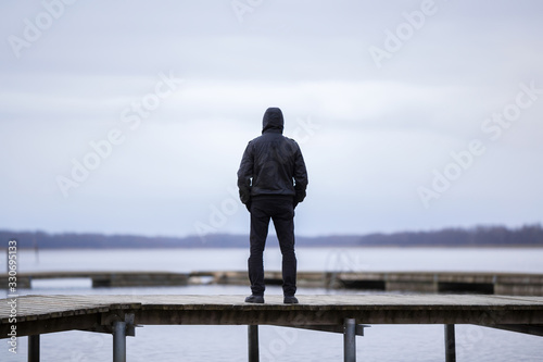 Obraz One young man in black clothes standing alone on wooden footbridge and staring at lake. Hooded guy. Peaceful atmosphere in nature. Enjoying fresh air in winter. Back view. - fototapety do salonu