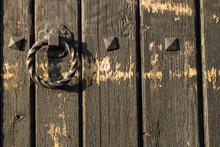 Twisted Door Handle On Wooden Door. The Door Handle Is Made Of Iron And Is Black.
