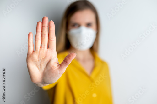 Fototapeta Virus mask woman wearing face protection in prevention for coronavirus showing gesture Stop Infection obraz
