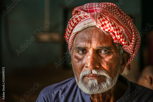Photo a depressed homeless refugee Arab grandfather wearing traditional turbine and fe