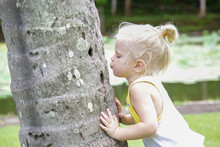 Young Child Hugging A Tree. Hu...