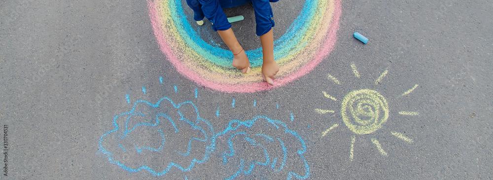 Fototapeta child draws with chalk on the pavement. Selective focus.