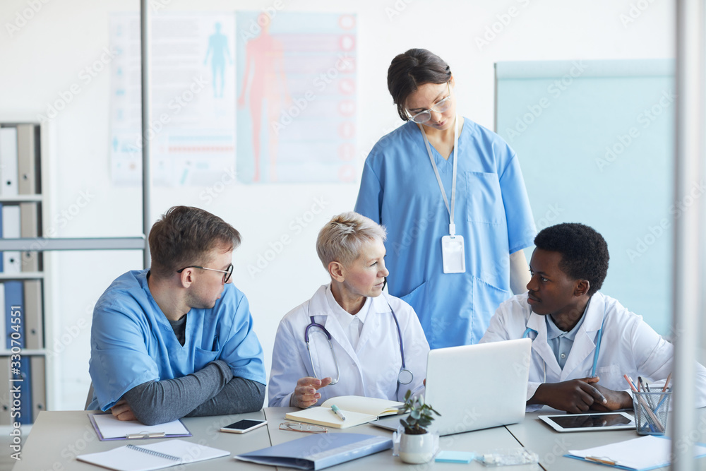 Fototapeta Multi-ethnic group of doctors communicating while sitting at desk with laptop in clinic office interior, copy space
