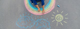 Fototapeta Rainbow - child draws with chalk on the pavement. Selective focus.