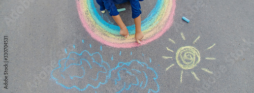 child draws with chalk on the pavement. Selective focus.