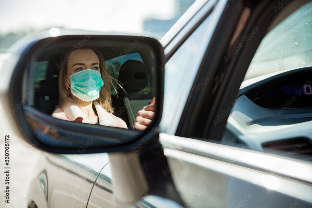 Fototapeta Woman in protective mask driving a car on road. Safe traveling.