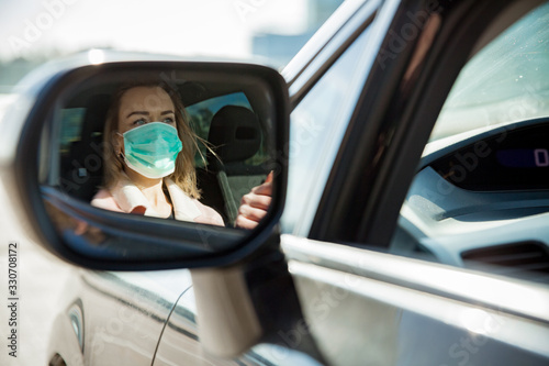 mata magnetyczna Woman in protective mask driving a car on road. Safe traveling.
