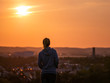 Rear view of woman enjoying beautiful sunset with the city of Augsburg in the background