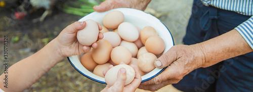 homemade eggs in grandmother's hands. Selective focus. Poster Mural XXL