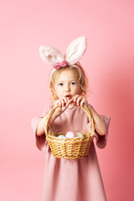 Happy Easter: A Little Girl In A Pink Dress And With Rabbit Ears Is Holding A Basket With Colorful Eggs In Her Hands.