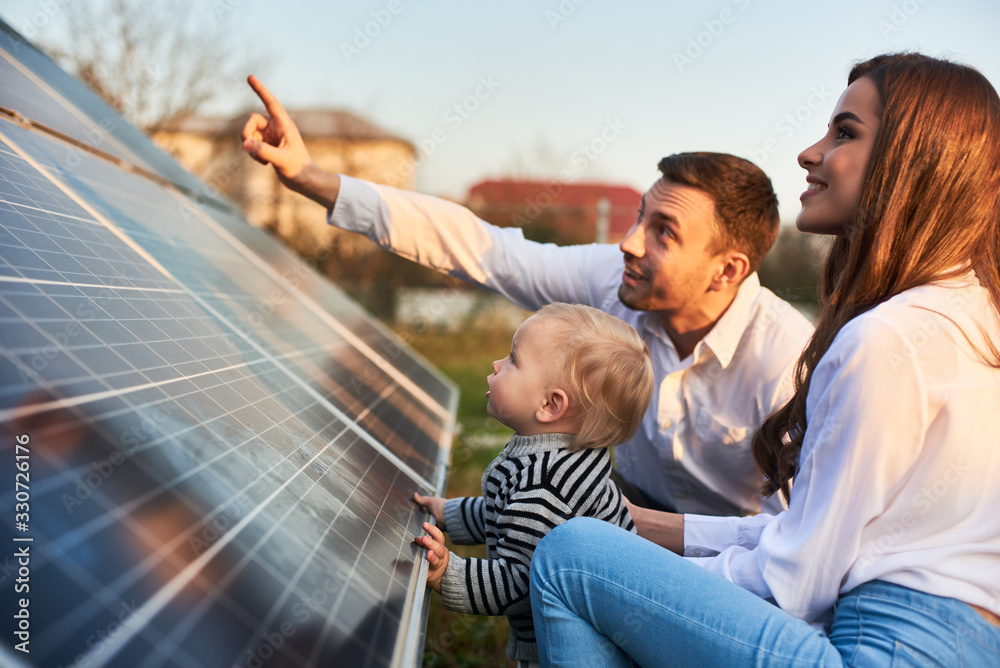 Fototapeta Man shows his family the solar panels on the plot near the house during a warm day. Young woman with a kid and a man in the sun rays look at the solar panels.