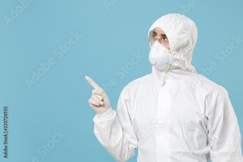 Man in white protective suit respirator mask isolated on blue background studio Canvas Print