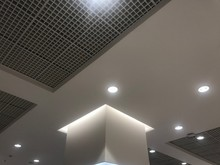 Suspended Grid False Ceiling With Gypsum Bulkhead Design And Column Coves With Indirect Lighting For A Lucrative Design View For A Shopping Mall And Emulsion Painted Ceiling Which Has Down Lights