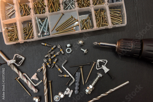 Foto set of tools on the table, a screwdriver with a set of drill bits and screws with bolts