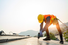 Roofer Worker In Protective Uniform Wear And Gloves,Using Air Or Pneumatic Nail Gun And Installing Concrete Roof Tile On Top Of The New Roof,Concept Of Residential Building Under Construction.