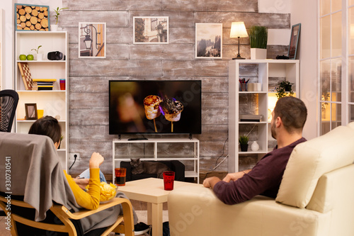 Photo Back view of couple in living room watching a movie on the TV
