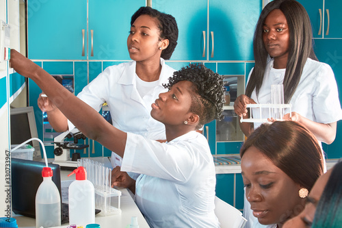Female African medical students or young graduates in research or medical test laboratory performing various testing on samples. Microscopic analysis biopsy, pcr nucleic acid test for coronavirus.