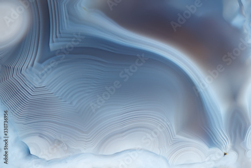 Photo Close- up texture of blue -white agate with a smooth concentric structure