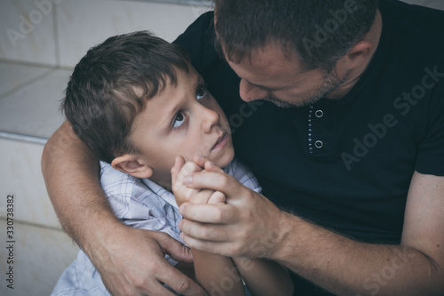 Portrait of young sad little boy and father sitting outdoors at the day time.