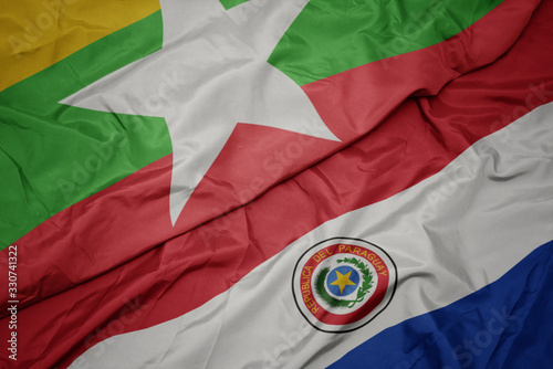 waving colorful flag of paraguay and national flag of myanmar. Canvas Print