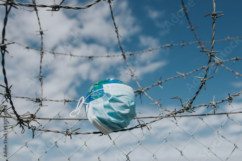 Fotografie, Tablou Surgical mask on Earth globe and barbed wire