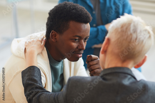 Obraz High angle view at young African-American man smiling gratefully to psychologist while while in support group circle, copy space - fototapety do salonu