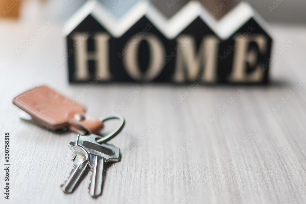 Fototapeta key and wooden Home model on table office. New House, Financial, Property insurance and real estate concepts