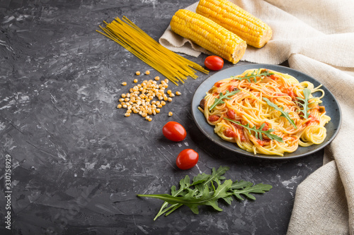 Photo Corn noodles with tomato sauce and arugula on a black concrete background