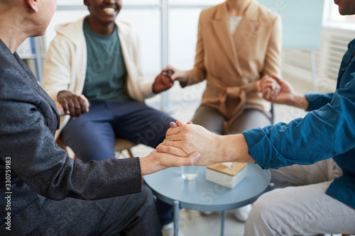 Fototapety, obrazy: Close up of multi-ethnic group of people holding hands in prayer while sitting in circle in support group, copy space
