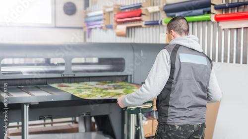 Fotomural Technician operator works on large premium industrial printer plotter machine